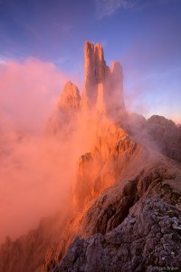 <p>Brilliant sunset light illuminates the Vajolet Towers in the Rosengarten as misty clouds swirl off the peaks.</p>